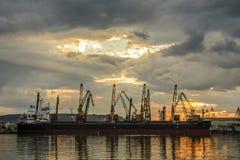 Fartyg som väntar för att laddas med kranar på solnedgången fotografering för bildbyråer