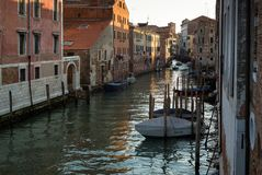 Fartyg som vilar en solnedgång längs en kanal i Venedig, Italien Royaltyfri Bild