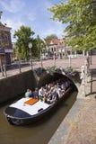 Fartyget av turister passerar mycket färgrika blommor på bron i centr Arkivfoto