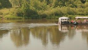 Fartyget med folk som svävar på floden stock video