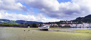 Fartyget strandade på en sandig strand på lågvatten Staden av Pontedeu Royaltyfri Bild