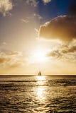 Fartygsegling och nivå som tar av på solnedgången Royaltyfri Bild