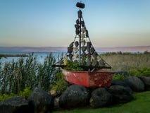 Fartygskulptur med seglar och rappar maskeringar av framsidor, havet av Galilee, Israel Arkivbilder