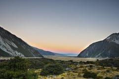 Farvälsol med berget/solnedgång på paradisställen i den södra Nya Zeeland/monteringskocken National Park arkivfoto