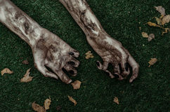 Fasa- och allhelgonaaftontema: Ruskiga levande dödhänder som är smutsiga med svart, spikar lögnen på det gröna gräset, den gå död royaltyfri foto