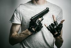 Fasa och skjutvapenämne: mördaren med ett vapen i hans hand i svarta handskar på en grå bakgrund i studion Royaltyfri Fotografi