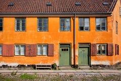Fasad av byggnad med gamla fönsterramar och trädörrar på den gamla gatan av Danmark Historiskt färgrikt hus royaltyfri bild