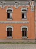 Fasad av byggnaden med fyra fönster Arkivbild