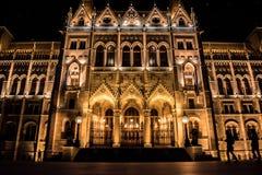 Fasad av den Budapest parlamentet på natten med konturer av turister som strosar, Ungern arkivfoto