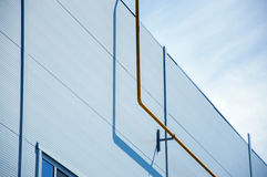 Fasad av den moderna vita byggnaden med det gula naturgasröret på den främre sikten och blå himmel på bakgrunden Arkivfoton