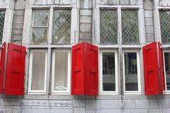 Fasad av en forntida byggnad med röda skydd och målat glassfönster, Utrecht, Nederländerna Fotografering för Bildbyråer
