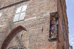 Fasad av en gammal bulding med en staty av den jungfruliga Maryen med J Royaltyfria Foton