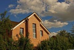 Fasad av en tegelstenbyggnad med fönster i gröna träd och buskar i trädgården Royaltyfria Bilder