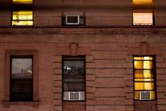 Fasad av en typisk r?dbrun sandstenhyreshus p? natten, i Harlem, New York City, NY, USA royaltyfri foto