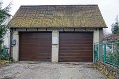 Fasad av ett privat garage med två bruna portar Arkivfoto