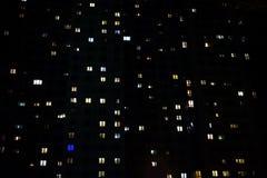 Fasad av ett stort mång--våning flerbostadshus med många belysningfönster i lägenhetnattsikt Royaltyfri Fotografi