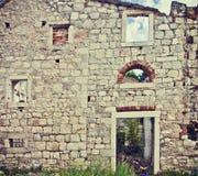 Fasad av förstörd och förfallen stenbyggnad Arkivbilder