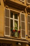 Fasad av gammal byggnad med blommor på öppet fönster och den soliga dagen i Paris Arkivfoton