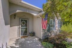 Fasad av hemmet med en amerikanska flaggan på väggen arkivbilder