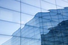 Fasad av modern glass byggnad med reflexioner av blå himmel och Royaltyfri Fotografi