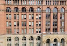 Fasad av tegelstenbyggnad med fönster och bågar Royaltyfria Bilder