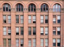 Fasad av tegelstenbyggnad med fönster och bågar Fotografering för Bildbyråer