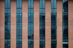 Fasad för tegelstenbyggnad med ett blått exponeringsglas för textur Arkivfoto
