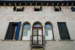 Fasad med det spröjsade fönstret av en forntida byggnad i Oderzo i landskapet av Treviso i Venetoen (Italien) royaltyfri foto