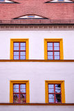 Fasad med fyra apelsin inramade fönster Royaltyfria Foton
