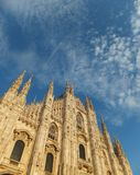 Fasada Duomo katedra w Mediolański trwanie wysokim przeciw niebieskiemu niebu z malutkimi białymi clounds, zaświecająca położenia zdjęcia royalty free