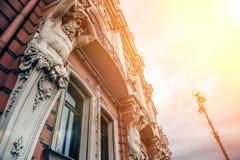 Fasada stary budynek w St Petersburg z statuami titans w świetle słonecznym Obrazy Royalty Free
