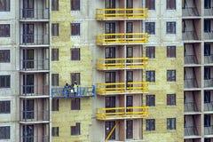 Fasadarbete och isolering av en flervånings- byggnad arkivbild