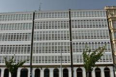 Fasaddetalj: fönster med vita wood gallerier och träd royaltyfria bilder