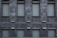 Fasade della costruzione di architettura dalla pietra grigia del granito con le finestre chiuse con i rollets del metallo immagine stock