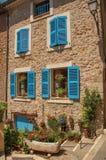 Fasaden av byggnad med fönster och blått stänger med fönsterluckor i Châteaudouble Royaltyfri Bild
