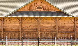 Fasaden av delen av en gammal träbyggnad med dekorativa kolonner och ett tak som göras av metallprofil, windowless vägg Fotografering för Bildbyråer