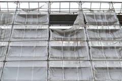 Fasaden av en hög byggnad med ett material till byggnadsställning och en textur Royaltyfri Bild