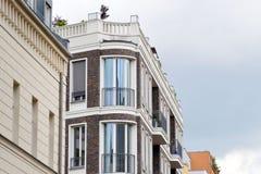 Fasaden av en hög byggnad med några fönster stängde lite ett träd Arkivfoto