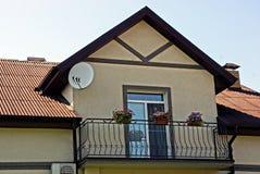 Fasaden av en modern byggnad med en järnbalkong och blomkrukor Royaltyfri Bild