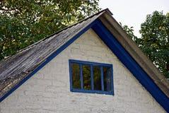 Fasaden av ett grått hus med ett litet fönster mot himlen och gräsplanen förgrena sig Royaltyfria Bilder