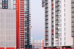 Fasaden av ett höghus med röda vita och gråa band Mång--våning byggnad mot den blåa himlen Bakgrund till fotografering för bildbyråer