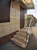 Fasaden av ett lägenhethus med en farstubro och dörren Royaltyfri Bild
