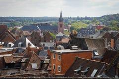 Fasaden av kyrkan i centret som omges av hus med röda tegelplattor på taket arkivbild