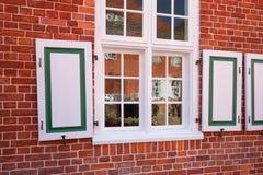 Fasaden av tegelstenväggen av byggnaden och dekorativt det samman med slutare royaltyfria foton