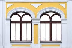 Fasaden av vit gul forntida byggnad med två isolerade välvda fönster förlöjligar upp royaltyfria bilder