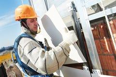 Fasadowy budowniczy instaluje płytkę na ścianie obraz royalty free