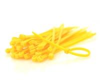 Fascette ferma-cavo gialle isolate contro fondo bianco fotografia stock libera da diritti