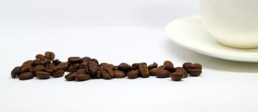 Fasci di caffè e di tazza bianca sulla tavola Immagini Stock Libere da Diritti