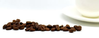 Fasci di caffè e di tazza bianca sulla tavola Fotografie Stock Libere da Diritti