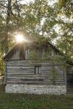 Fasci di legno e cottage di pietra accesi dai raggi del sole in una foresta fotografie stock libere da diritti
